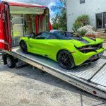 Green Mclaren being towed