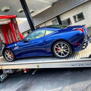 Blue Ferrari being towed
