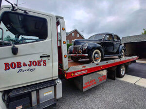 Antique black car being towed
